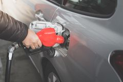 Closeup of man pumping gasoline fuel in car at gas station. Stock Images