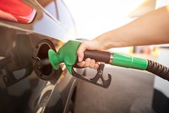 Closeup of man pumping gasoline fuel in car at gas station. Gas pump nozzle in the fuel tank of a gray car stock images