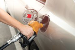 Closeup of man pumping gasoline fuel in car at gas station. Fuel Stock Photos
