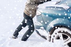 Closeup of man pushing car stuck in snow Stock Photography
