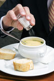 Closeup of man putting salt in a bowl of soup Royalty Free Stock Photography