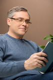 Closeup of man reading book and smiling. Stock Image