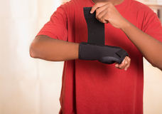 Closeup man in red shirt wearing black wrist brace support on right hand, tightening velcro using other arm Stock Photo