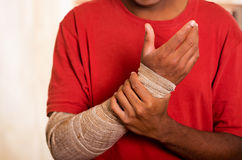 Closeup man in red shirt wearing large grey bandage over lower right arm, supporting with other hand Royalty Free Stock Images