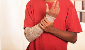 Closeup man in red shirt wearing large grey bandage over lower right arm, supporting with other hand Royalty Free Stock Photo