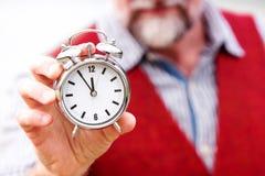 Closeup of man in red vest holding a clock Foto de archivo libre de regalías