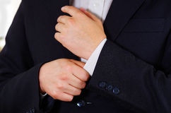 Closeup man's arm wearing suit, adjusting cufflinks using hands, men getting dressed concept Royalty Free Stock Photo