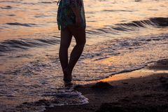 Closeup of a bare feet of a girl walking on the beach at sunset, with a wave edge, foaming gently underneath them, toned colors. Closeup of a man`s bare feet Royalty Free Stock Photography