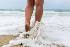 Closeup of a man`s bare feet walking at a beach, with a wave`s e Stock Photography