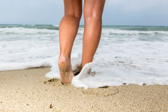 Closeup of a man`s bare feet walking at a beach, with a wave`s e Stock Images
