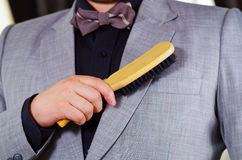 Closeup man's chest area wearing formal suit and bowtie, brushing off jacket using brush, men getting dressed concept.  Royalty Free Stock Images