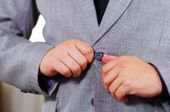 Closeup man's chest area wearing formal suit and tie, adjusting jacket buttons using hands, men getting dressed concept.  Stock Photo