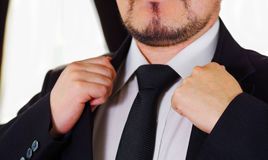 Closeup man's chest area wearing formal suit and tie, adjusting jacket collar using hands, men getting dressed concept.  Stock Images