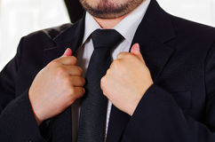 Closeup man's chest area wearing formal suit and tie, adjusting jacket collar using hands, men getting dressed concept.  Stock Image