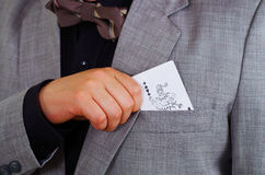 Closeup man's chest area wearing formal suit and tie, placing joker playing card in jacket pocket, men getting dressed. Concept Royalty Free Stock Images