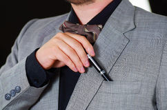 Closeup man's chest area wearing formal suit and tie, placing pen in jacket pocket, men getting dressed concept.  Stock Photography