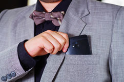 Closeup man's chest area wearing formal suit and tie, placing phone in jacket pocket, men getting dressed concept.  Stock Photos