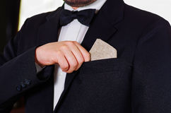 Closeup man's chest area wearing formal suit and tie, placing small liquor bottle in jacket pocket, men getting dressed. Concept Stock Images