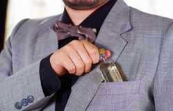 Closeup man's chest area wearing formal suit and tie, placing small liquor bottle in jacket pocket, men getting dressed. Concept Stock Photos