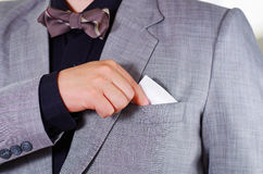 Closeup man's chest area wearing formal suit and tie, placing tissue in jacket pocket, men getting dressed concept.  Stock Photography