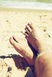 Closeup of man's feet at the beach sand Royalty Free Stock Images