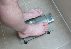 Man`s feet on weight scale -. Closeup of man`s feet on weight scale Stock Photos
