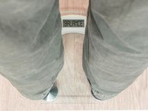 Man`s feet on weight scale - Balance. Closeup of man`s feet on weight scale - Balance Royalty Free Stock Image
