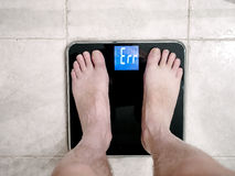 Closeup of man's feet on weight scale indicating error Royalty Free Stock Photo