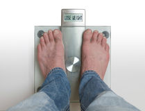 Man`s feet on weight scale - Lose weight. Closeup of man`s feet on weight scale - Lose weight Royalty Free Stock Photos