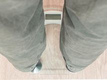 Man`s feet on weight scale -. Closeup of man`s feet on weight scale Royalty Free Stock Images