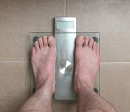 Man`s feet on weight scale -. Closeup of man`s feet on weight scale Royalty Free Stock Photo