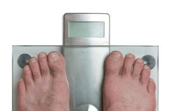 Man`s feet on weight scale -. Closeup of man`s feet on weight scale Stock Images