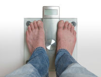 Man`s feet on weight scale -. Closeup of man`s feet on weight scale Stock Image