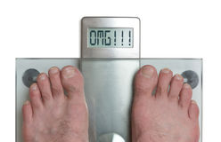 Man`s feet on weight scale - OMG. Closeup of man`s feet on weight scale - OMG Stock Images