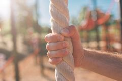 Closeup of Man`s hairy arms grasping or holding a rope indicating someone climbing in a gym blurred background stock photo