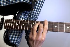 Closeup of mans hand on guitar frets Royalty Free Stock Image