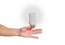Closeup of man's hand holding energy saving lamp. Glows brightly Royalty Free Stock Photos