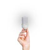 Closeup of man's hand holding energy saving lamp. Glows brightly Stock Photo