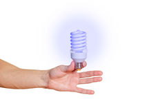 Closeup of man's hand holding energy saving lamp. Glows brightly Royalty Free Stock Images