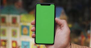 Closeup of a man`s hand holding a mobile telephone with a vertical green screen on the streets. Children`s store in the stock video