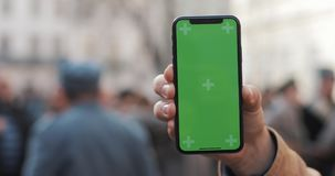 Closeup of a man`s hand holding a mobile telephone with a vertical green screen on the streets. Military soldiers in the. Background stock footage