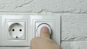 Closeup of a man's hand inserting an electrical plug into a wall socket. stock video footage