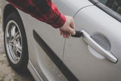 Closeup of a man's hand inserting a key into the door lock of a car. Unrecognizable white man opens vehicle door by key. Casually stock photo