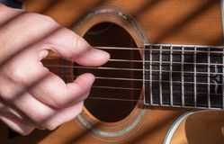 Closeup of man`s hand playing acoustic guitar stock photo
