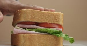 Closeup of man`s hand press the sandwich. Finish movement to sandwich preparation royalty free stock photos
