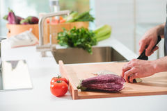 Closeup man's hands cutting vegetables in a kitchen. Man is cutting tomatoes and eggplants on a work surface in a kitchen Royalty Free Stock Image