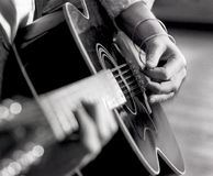 Closeup man`s hands, fingers, strumming acoustic guitar with pick royalty free stock image