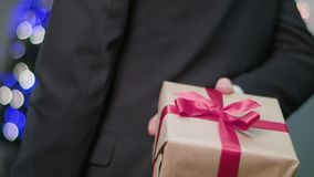 Man`s Hands Holding and Giving a Christmas Gift. Closeup of a man`s hands holding a Christmas gift or present behind the man`s back and giving it to someone. A Royalty Free Stock Photo