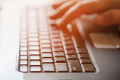 Closeup of man's hands typing on keyboard. Image can be used for Stock Images