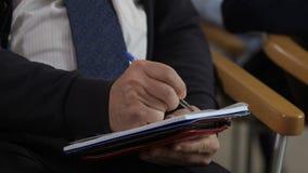 Closeup man`s hands writing information at seminar stock video footage